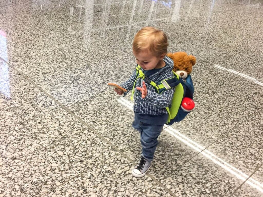 image of toddler walking in airport with toddler carry-on