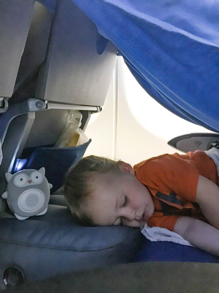 image of toddler sleeping on airplane on inflatable airplane travel bed