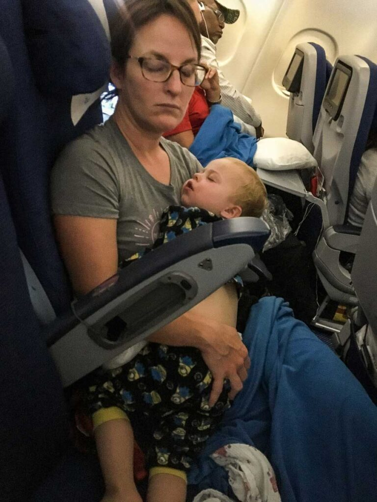 image of mother flying with toddler on lap