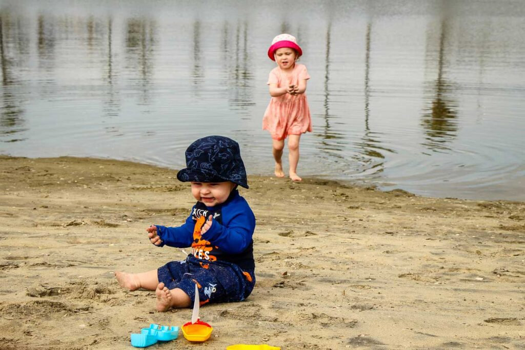 A baby and toddler play on the beach near Mission Beach, San Diego