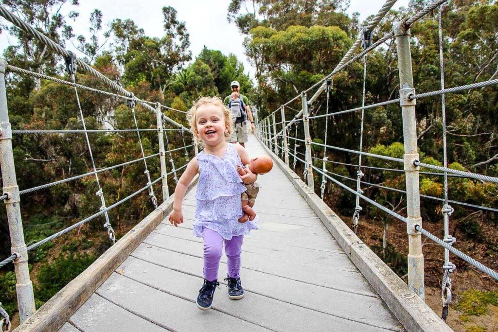A toddler races across the Spruce Street Suspension Bridge near Balboa Park in San Diego