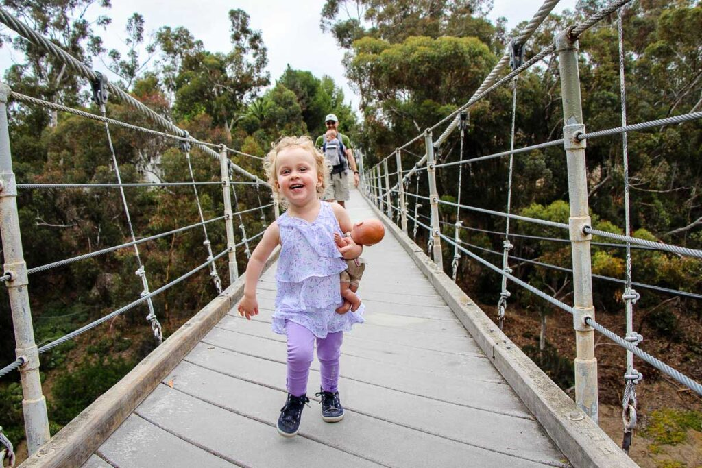 A toddler runs across the Spruce Street Suspension Bridge near Balboa Park, San Diego
