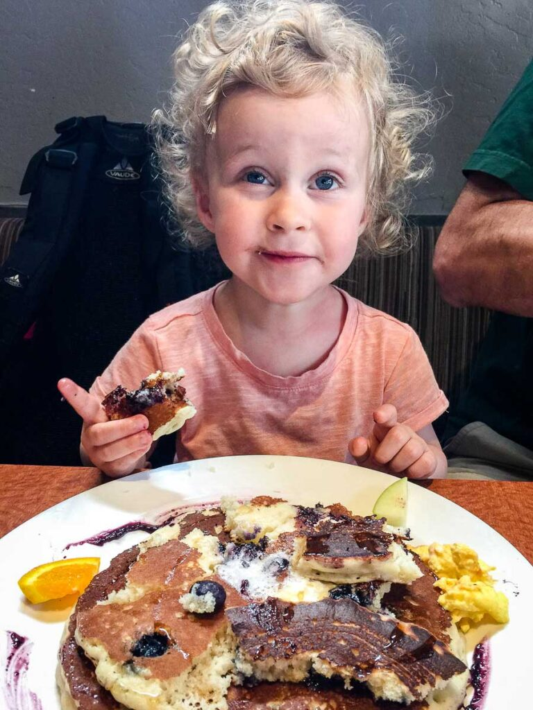 A toddler enjoys blueberry pancakes for breakfast at the Mission Restaurant, San Diego