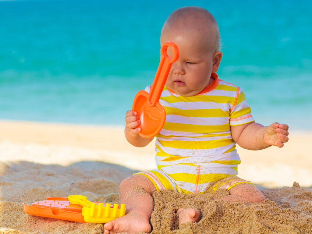 baby on beach playing with baby beach toys