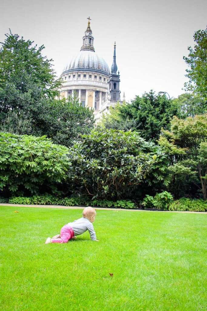 Baby crawling on grass in front of St Pauls Cathedral in London