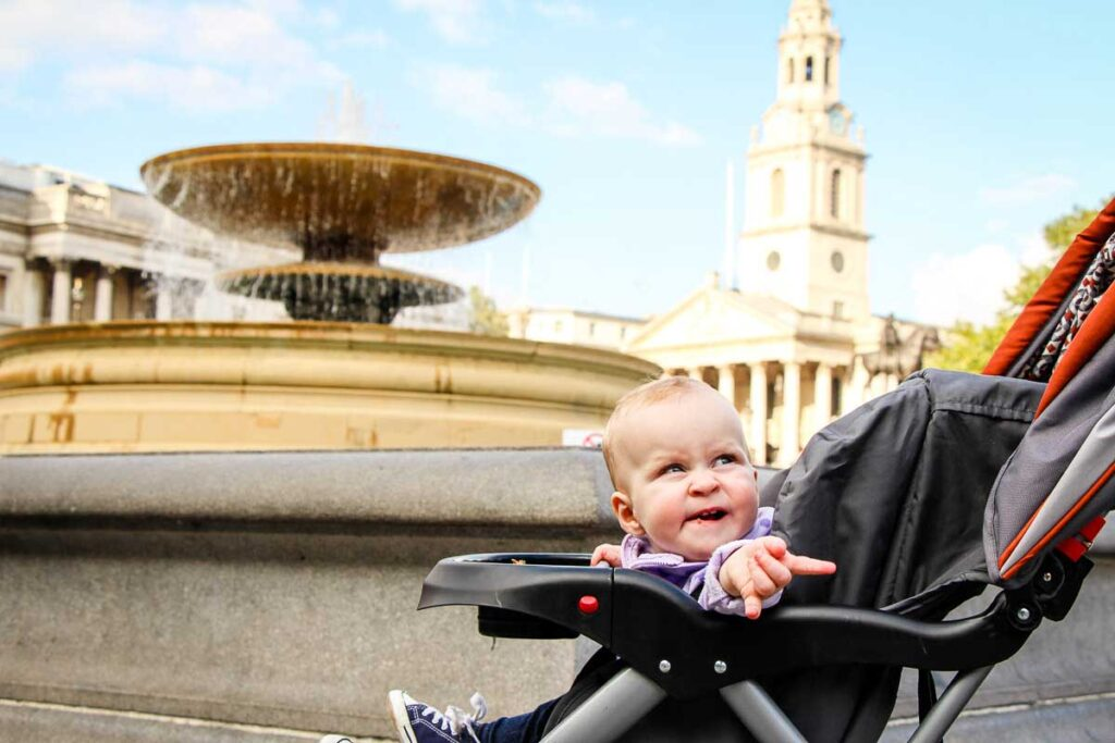 baby in stroller in front of fountain in Trafalgar Square London