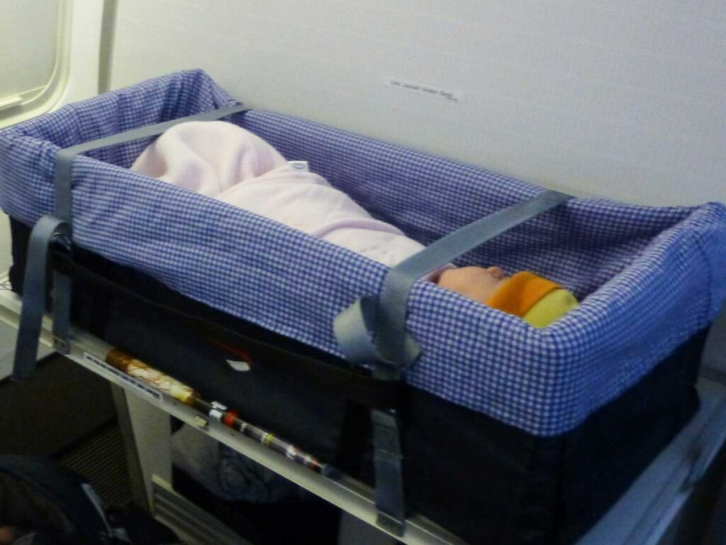 baby sleeping in airplane bassinet