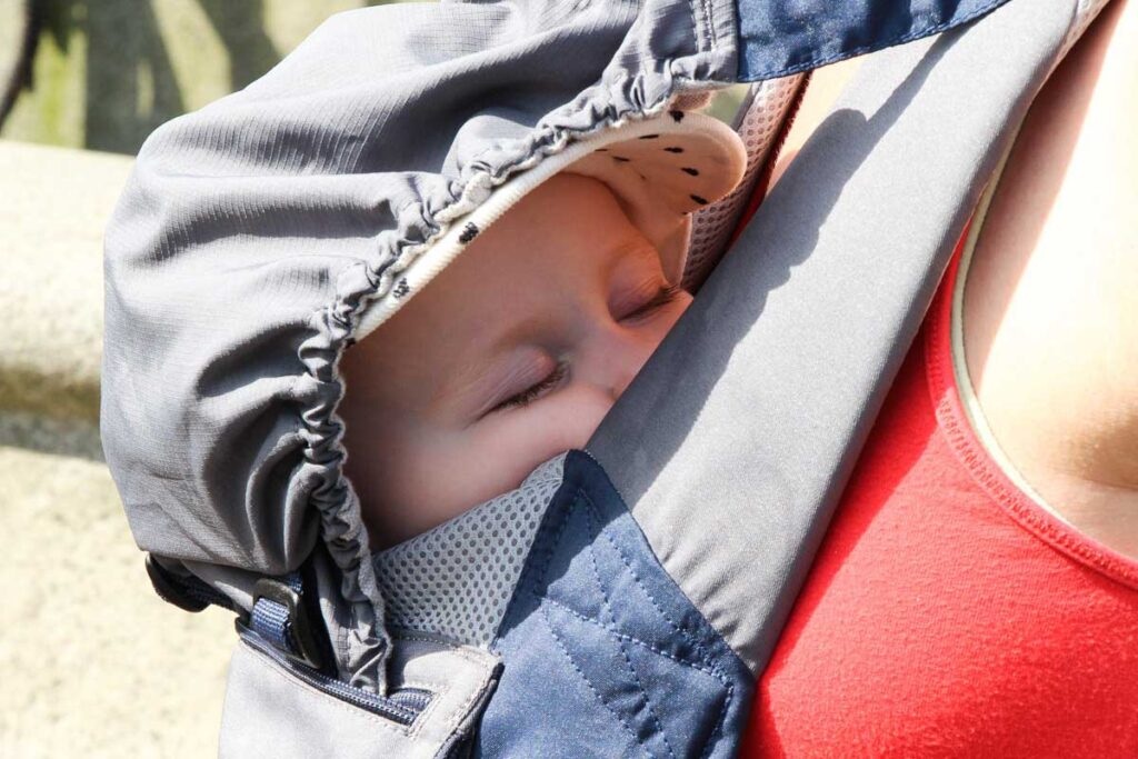 baby sleeping in baby carrier - one of the must-have baby travel gear items