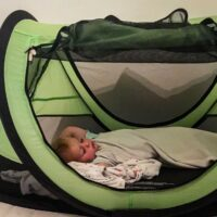 Toddler sleeping in KidCo PeaPod Plus toddler travel bed