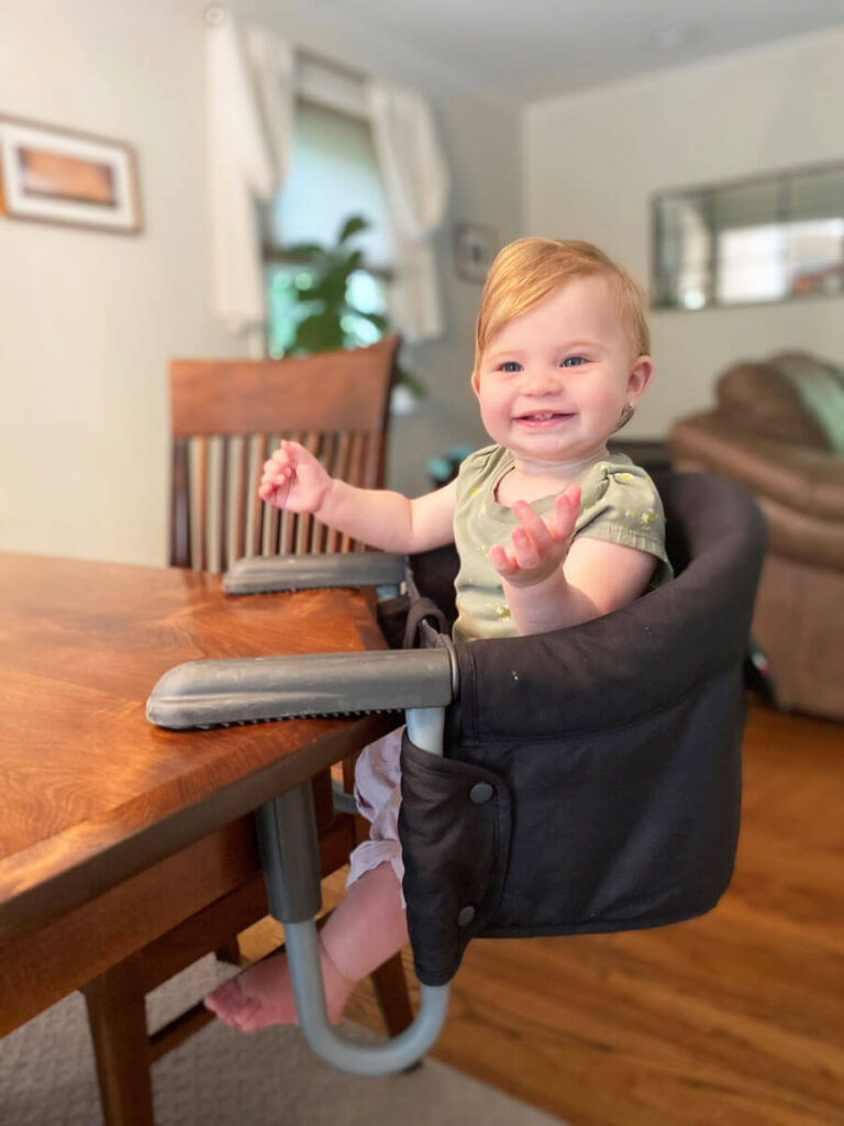baby sitting in Inglesina high chair - baby seat that attaches to table