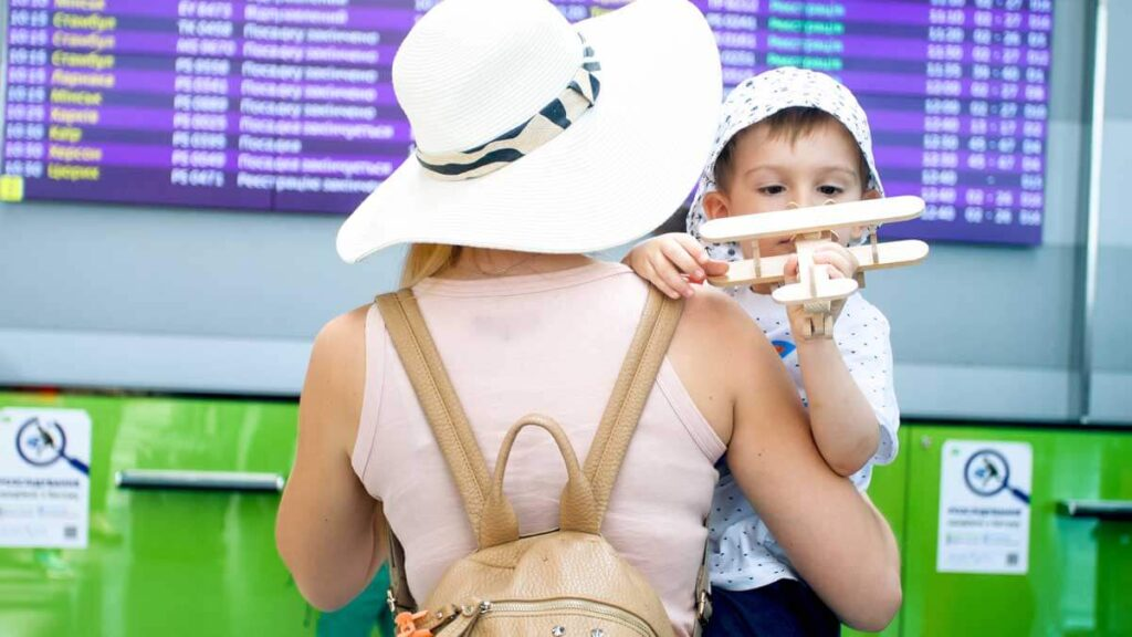 Woman at airport carrying child with a backpack style diaper bag