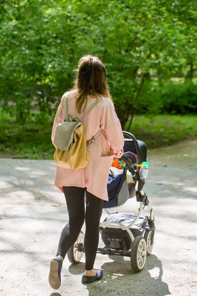 Woman pushing stroller carrying best baby backpack diaper bag