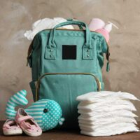 best backpack baby diaper bag surrounded by diapers and baby essentials