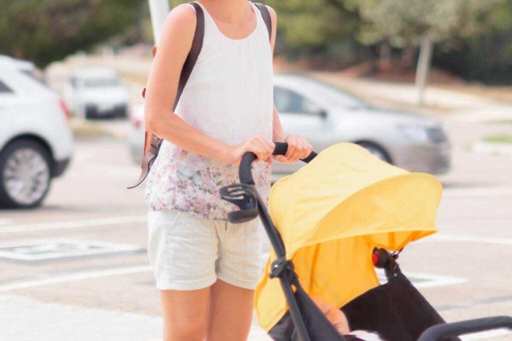 Woman pushing stroller carrying diaper bag backpack