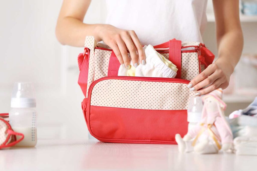 Woman packing a diaper bag with baby essentials