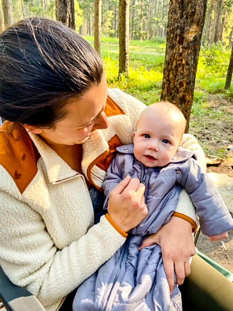mother hold baby wearing camping sleeping bag for baby