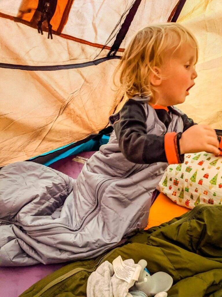 toddler crawling in tent wearing toddler sleeping bag for camping