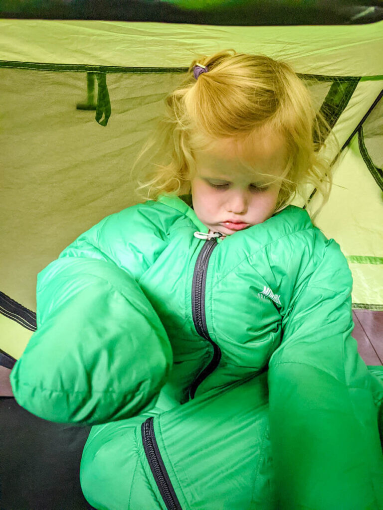 toddler wearing a Morrison Outdoors toddler sleeping bag in Peapod Plus toddler bed for camping