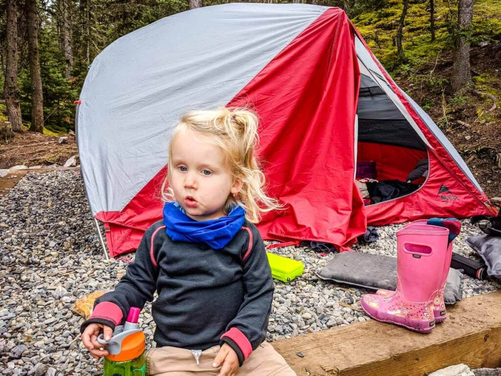 Toddler outside of the tent with camping gear around