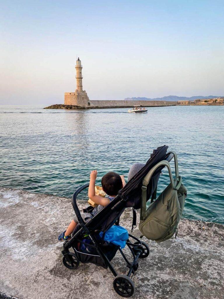 toddler in inglesina stroller in Crete overlooking ocean