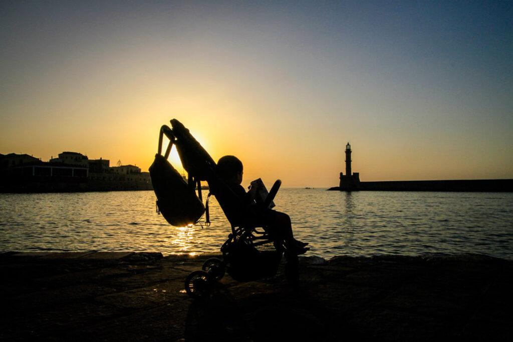 Toddler in travel stroller at sunset in Greece