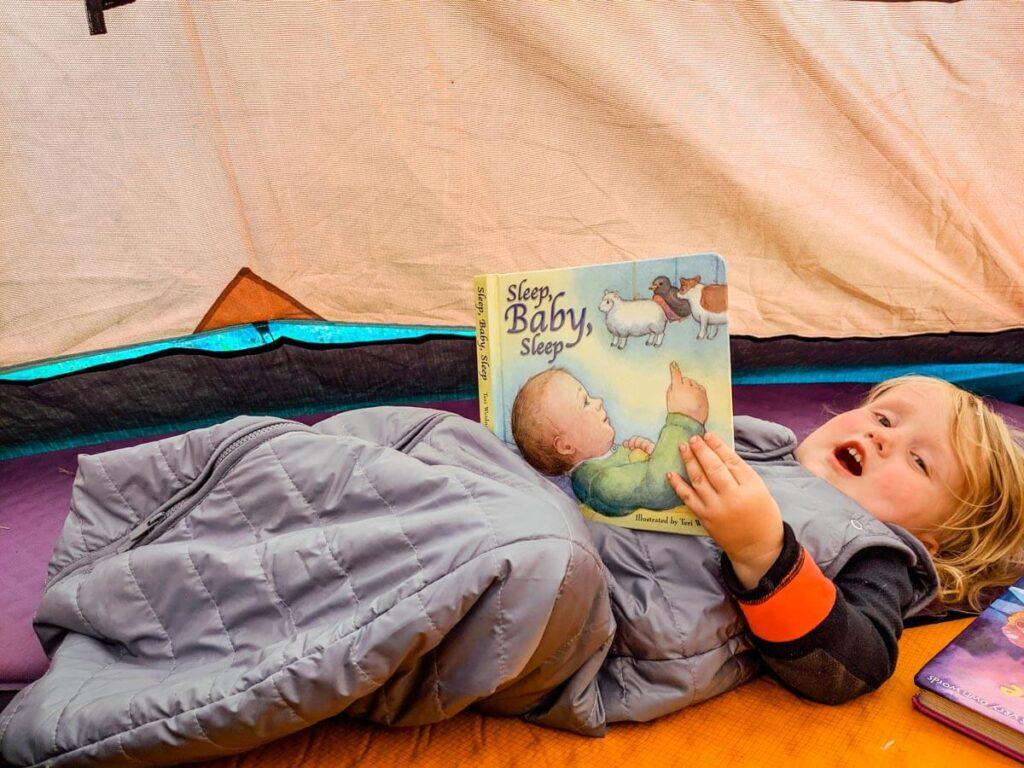 Toddler reading book and wearing Baby Deedee toddler sleeping bag for camping