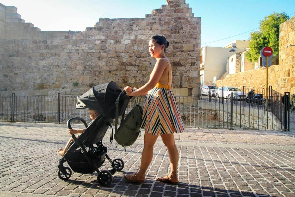 Mother pushing foldable compact stroller in Greece