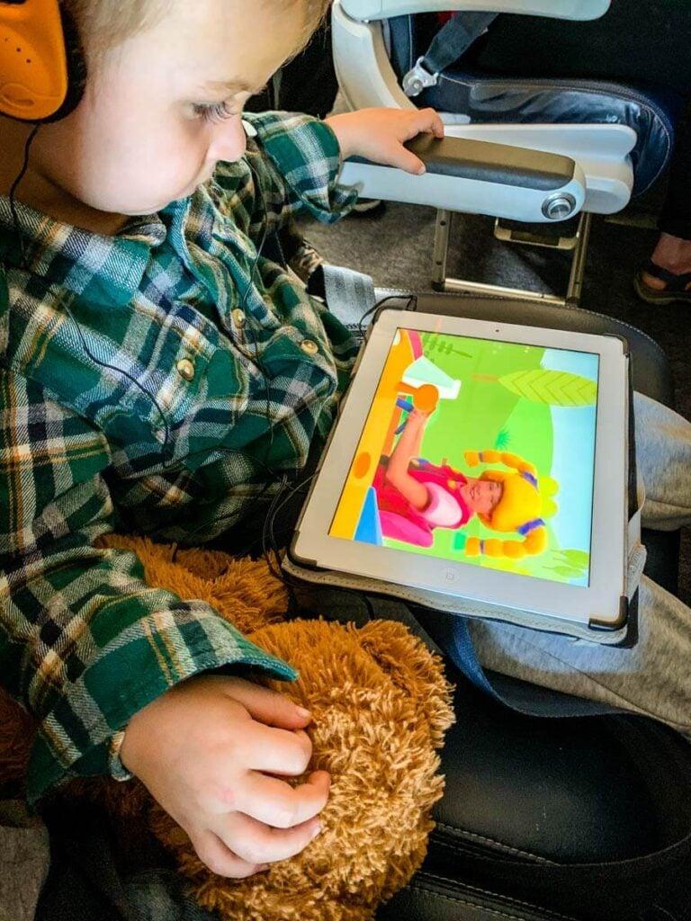 toddler watching ipad while wearing toddler airplane headphones