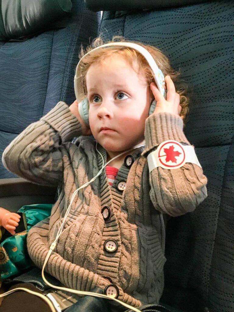 toddler on airplane wearing toddler headphones for plane