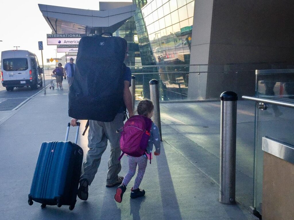 father and toddler walking into airport carrying JL Childress car seat bag for travel