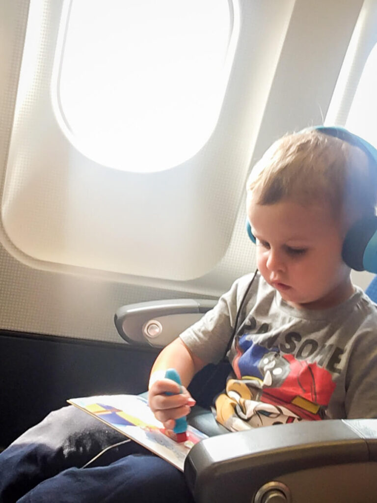 toddler on airplane coloring while wearing toddler headphones for airplane