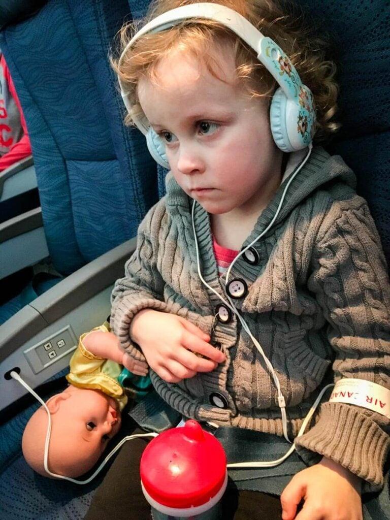 toddler on airplane wearing toddler safe headphones