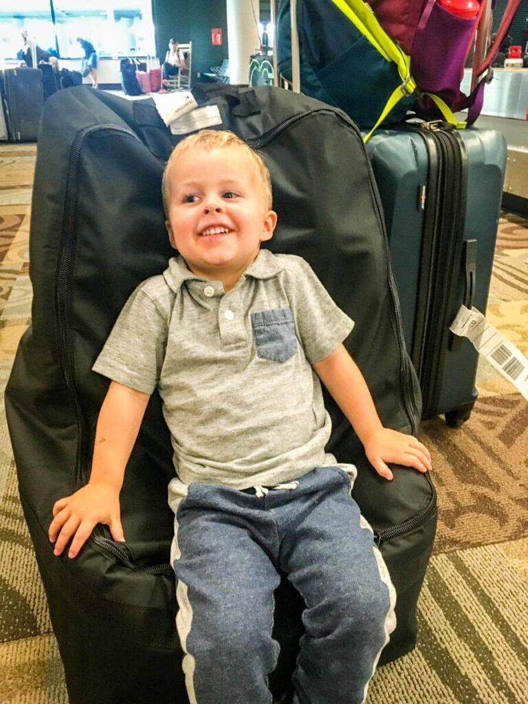 toddler in airport sitting on car seat in car seat bag for flying