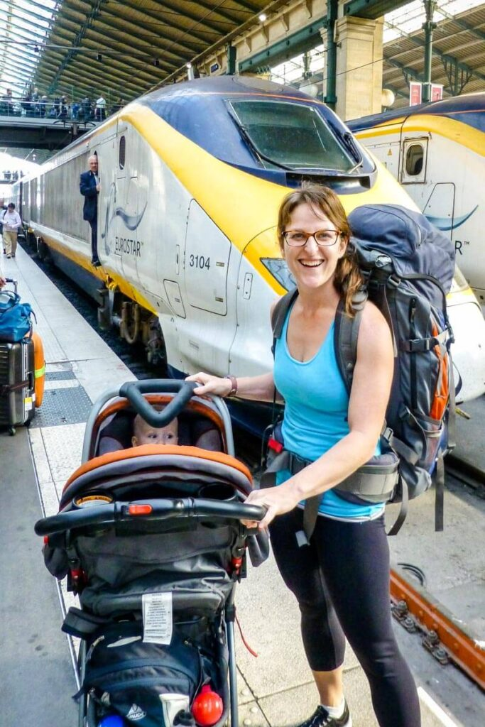 mother next to travel system with baby in car seat on stroller