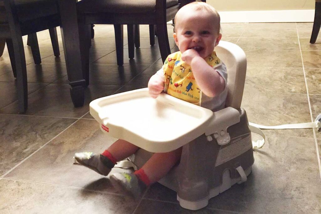 Baby in Booster Seat on floor